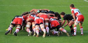 """A scrum (short for scrummage) is a method of restarting play in rugby that involves players packing closely together with their heads down and attempting to gain possession of the ball."""